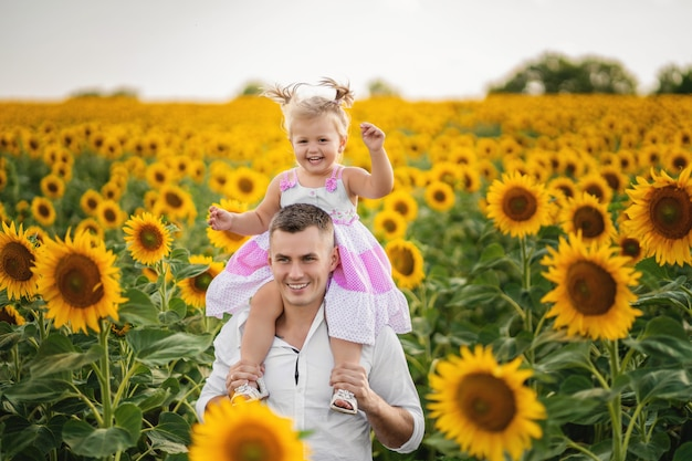 Ojcuje bawić się i wiruje z jego córką w polu słonecznik.