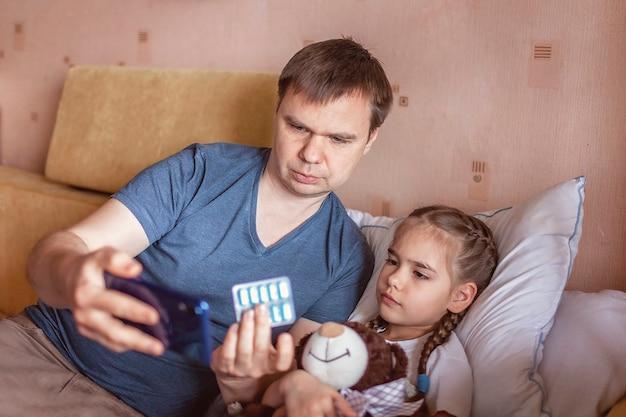 Ojcuje patrzeć ekran smartphone i konsultuje z lekarką online w domu