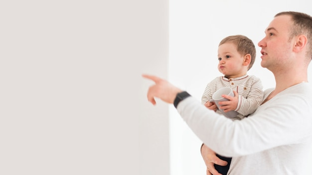 Ojcuje pokazywać dziecku coś z kopii przestrzenią