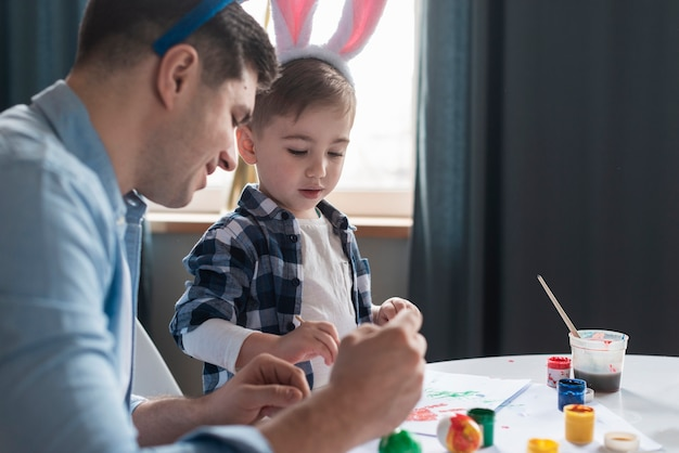 Ojcuje pokazywać jego synowi jak malować easter jajka