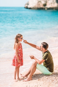 Ojcuje stosować krem przeciwsłoneczny jego córka przy tropikalną plażą