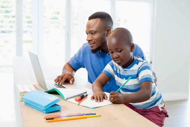 Ojcuje używać laptop i syna robi jego pracie domowej w żywym pokoju