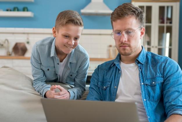 Ojcuje z szkłami i dzieckiem patrzeje laptop