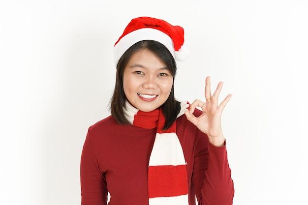 Ok znak pięknej azjatyckiej kobiety noszącej czerwony golf i santa hat na białym tle