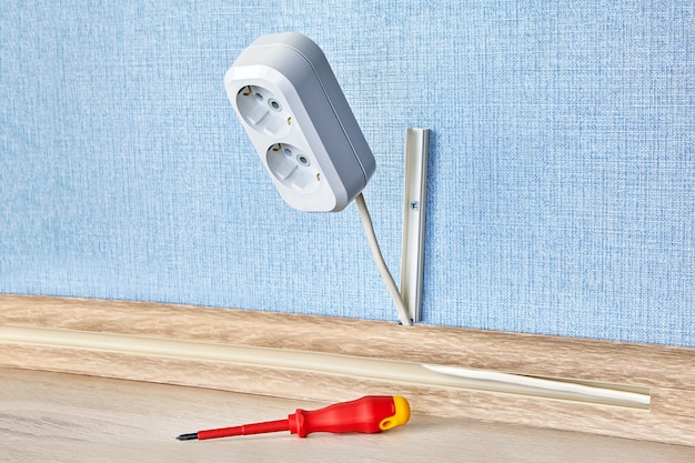 Okablowanie domu z wtyczką elektryczną ze śrubokrętem na podłodze.