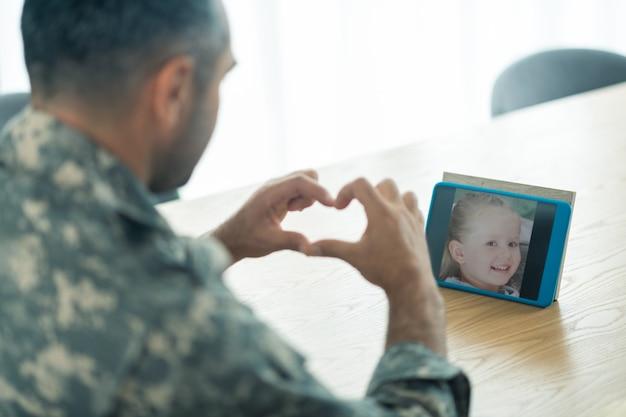 Okazywanie całej miłości. oficer wojskowy w mundurze pokazujący całą swoją miłość do córki podczas wideoczatu