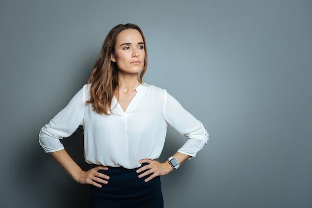 Okazywanie zaufania. poważna piękna inteligentna bizneswoman opierając ręce na biodrach i pokazując pewność siebie, stojąc na szarym tle