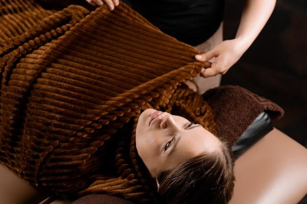 Okład całego ciała po masażu czekoladowym. zabieg kosmetyczny dla modelki w spa.