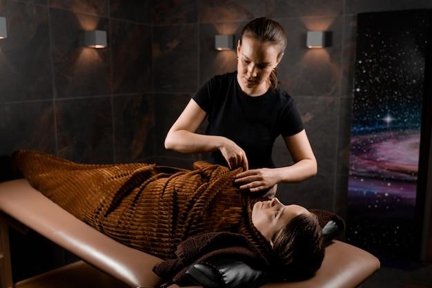 Okład całego ciała w ciepły koc po zabiegu kosmetycznym masażu czekoladowego dla modelki w spa.