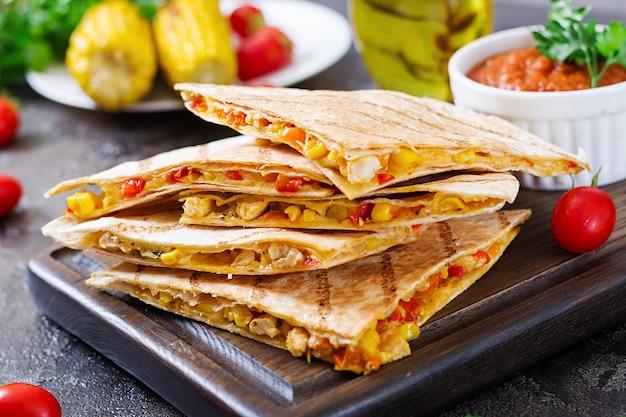 Okład meksykański quesadilla z kurczakiem, kukurydzą i słodką papryką i sosem pomidorowym.