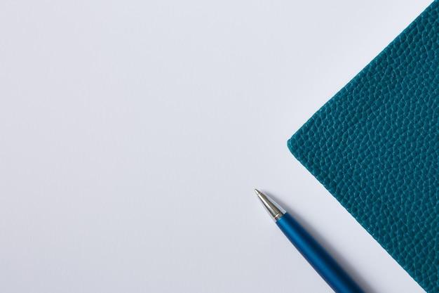 Okładka zielonego zeszytu, pamiętnika lub książki na białym papierze i niebieski metalowy długopis leżał płasko
