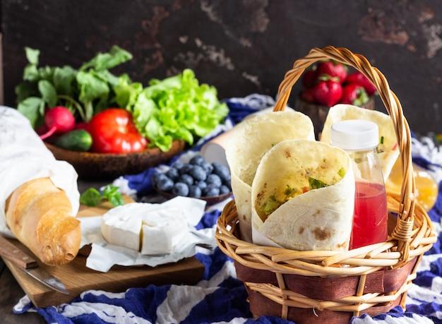 Okłady z tortilli z pieczonym kurczakiem i warzywami, sokami, warzywami i jagodami, bagietką i serem.