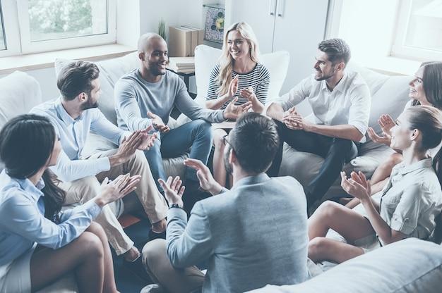 Oklaskując ich osiągnięcia. grupa młodych wesołych ludzi siedzących w kręgu i bijących brawo, podczas gdy jeden mężczyzna gestykuluje i uśmiecha się
