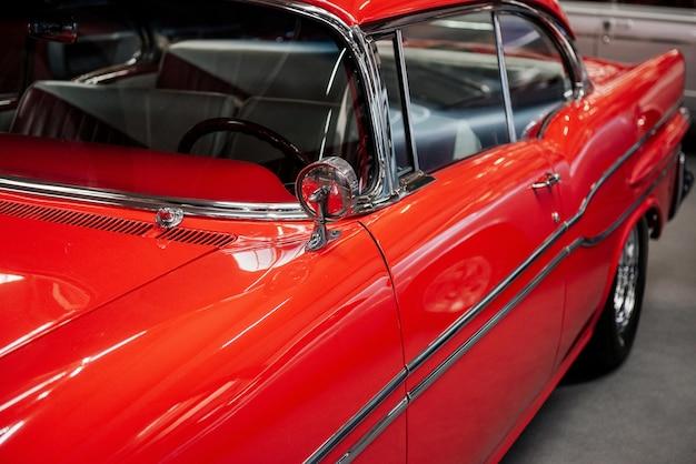 Okna, drzwi i boki tego czerwonego samochodu w stylu retro są idealnie wypolerowane