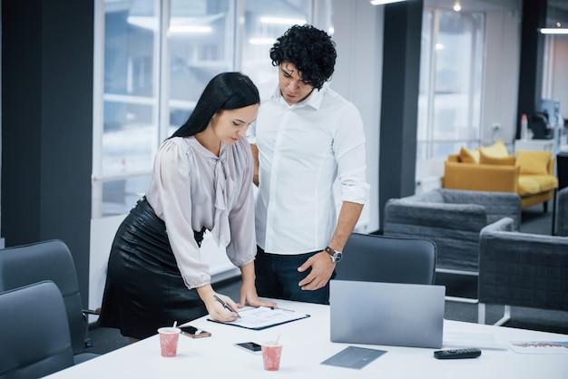 Okna i łóżka z tyłu. kędzierzawy facet i brunetka omawiają szczegóły kontraktu w nowoczesnym biurze