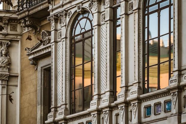 Okna kratowe ozdobnej elewacji neoklasycystycznego budynku