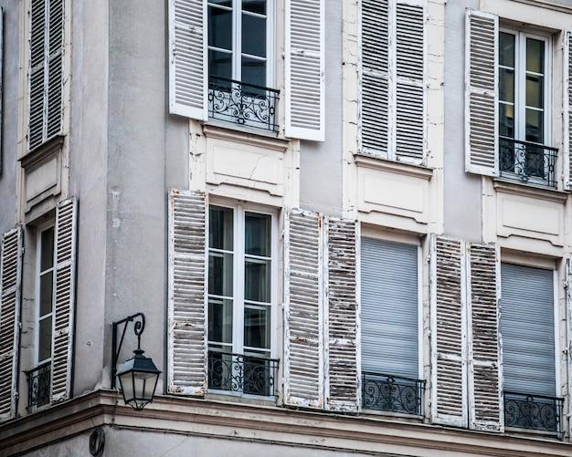Okna starego budynku mieszkalnego w słońcu w ciągu dnia w paryżu, francja