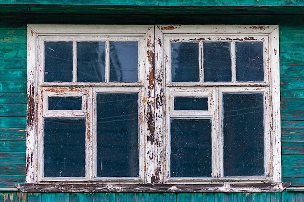 Okna starego odrapanego drewnianego domu