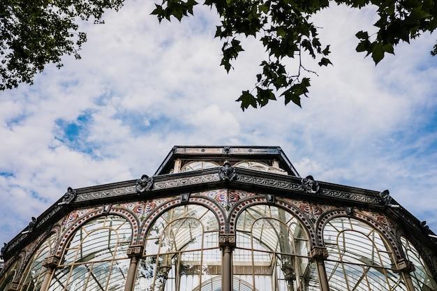 Okna szklanego pałacu parku retiro w madrycie, ze ścianą nieba z chmurami.