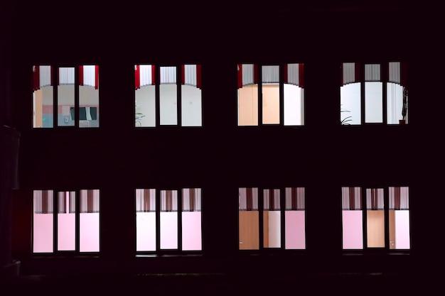 Okna w budynku mieszkalnym świecą w nocy. zdjęcie wysokiej jakości
