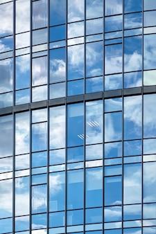 Okna wieżowca z odbiciem błękitnego nieba i białych chmur