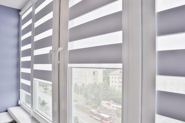 Okna z otwartymi nowoczesnymi żaluzjami poziomymi do wnętrz