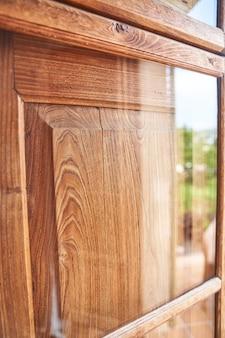 Okno drewniane i szklane z odbiciem od zewnątrz