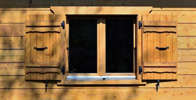 Okno i okiennice na drewnianej elewacji tradycyjnego alpejskiego domku