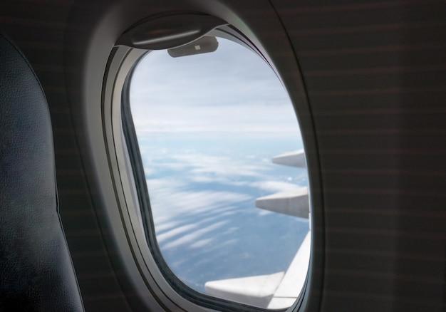 Okno od strony pasażera z lecącym skrzydłowym samolotem