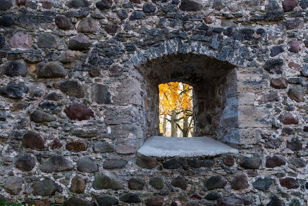 Okno w kamiennej ścianie w jesień krajobrazie