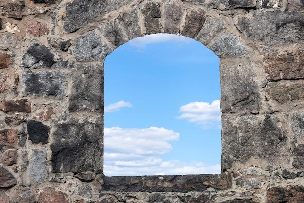 Okno w starej szarej kamiennej ścianie z błękitnym niebem i chmurami