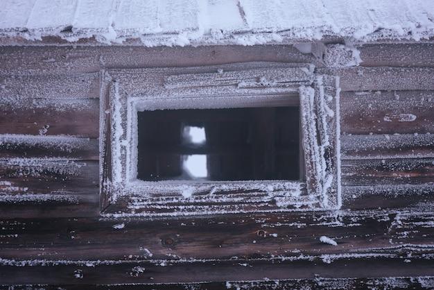 Okno w starym domu. szron na drewnianych ścianach. tonowanie kolorów