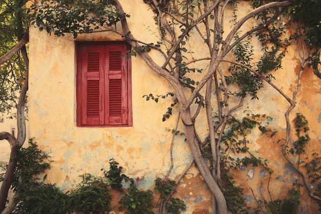 Okno z czerwoną żaluzją anafiotika w miasteczku ateny, grecja.
