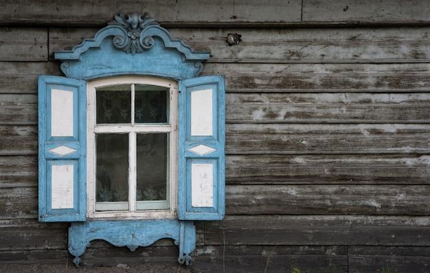 Okno z drewnianą rzeźbioną architekturą w starym drewnianym domu w starym rosyjskim mieście.