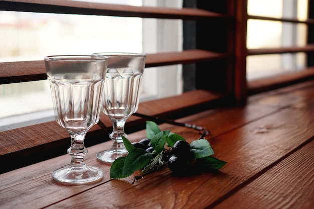 Okno z drewnianym przytulnym parapetem - puste szklanki i kwiatowy wystrój