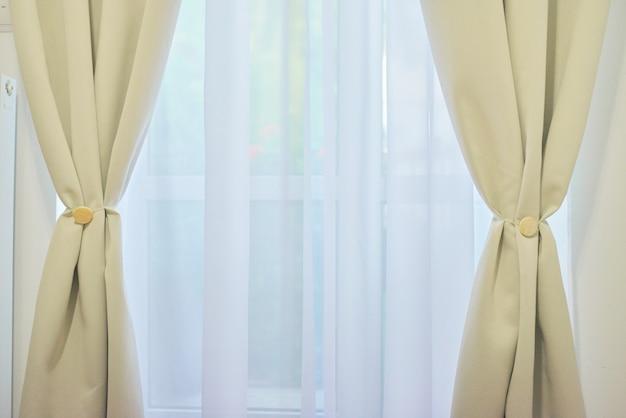 Okno z jasnoszarymi otwartymi zasłonami i białym welonem