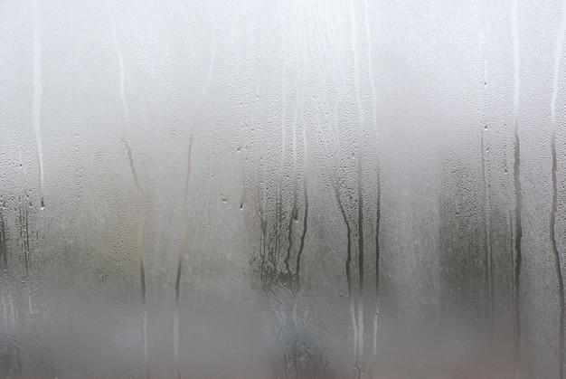 Okno z kondensatem lub parą po ulewnym deszczu, dużej teksturze lub tle