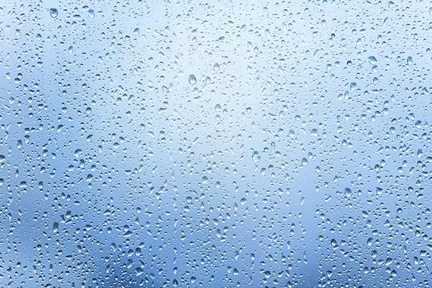 Okno z kroplami po ulewnym deszczu, krople wody na szkle jako tło lub tekstura