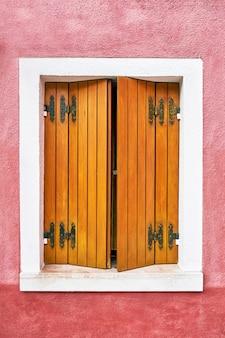 Okno z ładnymi drewnianymi okiennicami na czerwonej ścianie. włochy, wenecja, burano