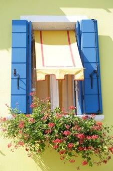 Okno z niebieskimi drewnianymi okiennicami i jedną markizą na pomalowanej na żółto ścianie, na parapecie, doniczce z czerwonymi kwiatami, na wyspie burano, wenecja, włochy