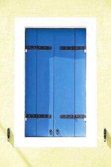 Okno z niebieskimi drewnianymi okiennicami na pomalowanej na żółto ścianie, na wyspie burano, wenecja, włochy