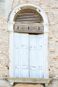 Okno z niebieskimi drewnianymi okiennicami na uszkodzonej ścianie z cegły, wenecja, włochy