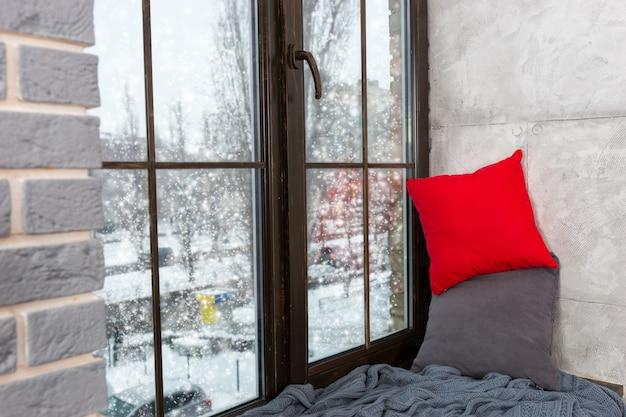 Okno z parapetem z poduszkami i kocem w sypialni w stylu loft, za oknem śnieg