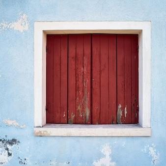 Okno z zamkniętą czerwoną żaluzją na niebieskiej ścianie. włochy, wenecja, wyspa burano.