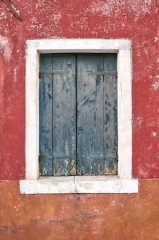 Okno z zamkniętą starą zieloną żaluzją na czerwonej ścianie. włochy, wenecja, wyspa burano.