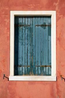 Okno z zamkniętą zieloną żaluzją na czerwonej ścianie. włochy, wenecja, wyspa burano.