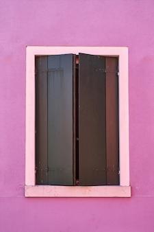 Okno z zieloną żaluzją na różowej ścianie. włochy, venicw, wyspa burano.