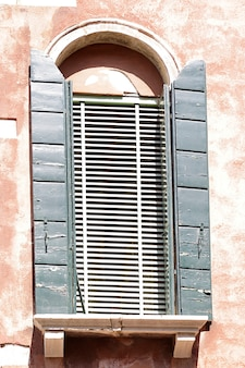 Okno z zielonymi drewnianymi okiennicami na różowej uszkodzonej ścianie