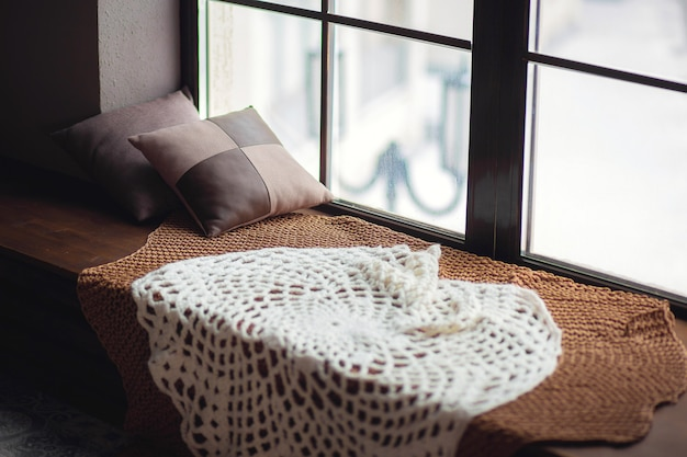 Okno zimowe. ciepła dzianinowa narzuta na parapecie z poduszkami. przytulne miejsce na oknie