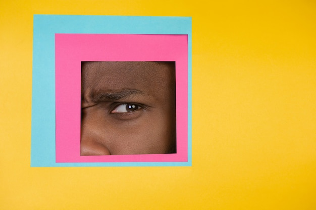 Oko afro-amerykańskiego mężczyzny zerkające przez plac na żółtym tle